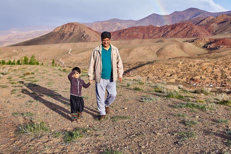 Mens die op bergplateau lopen met weinig jongen, Abyaneh, Iran royalty-vrije stock foto