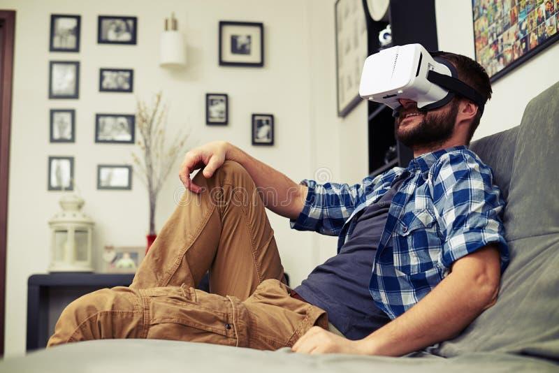 Mens die op comfortabele bank rusten die VR-hoofdtelefoonglazen dragen stock foto