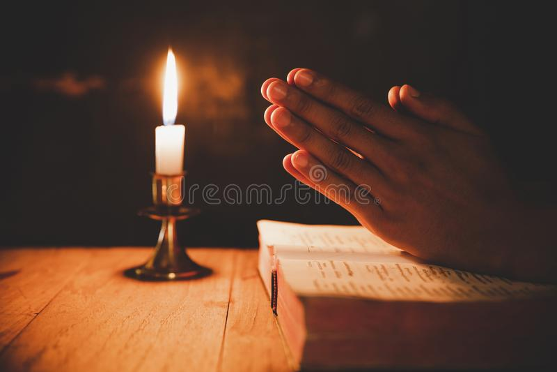 Mens die op de Bijbel in de lichte kaarsen selectieve nadruk bidden royalty-vrije stock foto