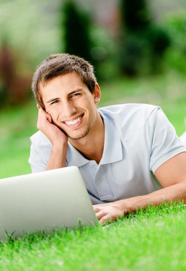 Mens die op de graswerken bij laptop liggen stock foto