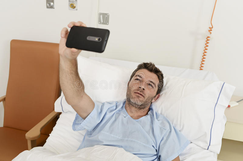 Mens die op de kliniek liggen die van het bedziekenhuis mobiele telefoon houden die zelfportret selfie foto nemen droevige gedepr royalty-vrije stock foto's