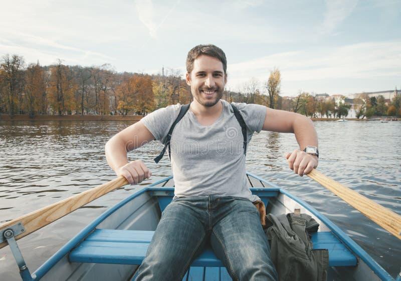 Mens die op de rivier roeien stock foto's