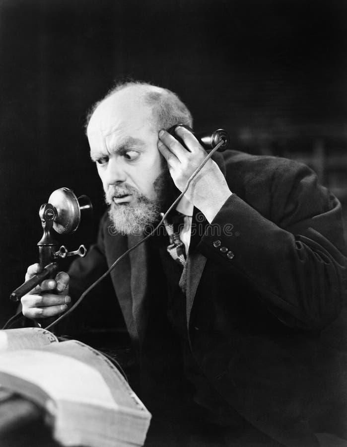 Mens die op de telefoon spreken die intens kijken (Alle afgeschilderde personen leven niet langer en geen landgoed bestaat Levera royalty-vrije stock foto's