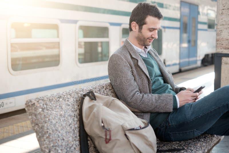 Mens die op de trein gezet in een station wachten stock foto's