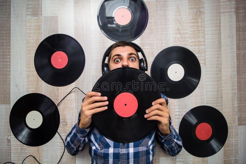 Mens die op de vloer met hoofdtelefoons onder vinylverslagen liggen stock afbeeldingen