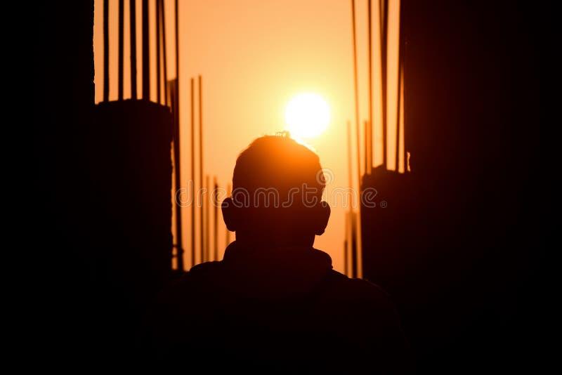 Mens die op de Zonsondergang van een in aanbouw Plaatsfoto letten stock fotografie