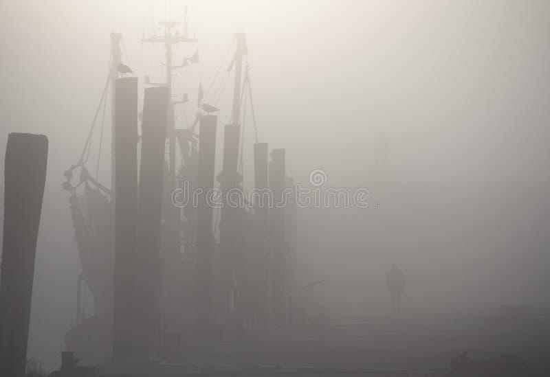 Mens die op Dok voorbij Masted-Schip in Mist lopen stock afbeelding