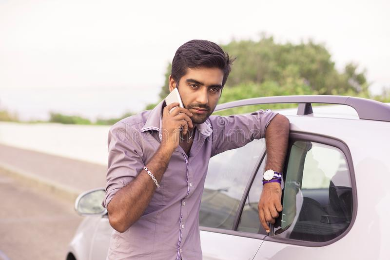 Mens die op een celtelefoon spreken die op de deur van zijn auto leunen stock afbeeldingen