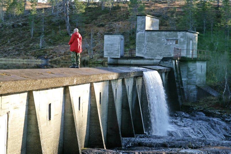 Mens die op een dam vissen royalty-vrije stock afbeeldingen