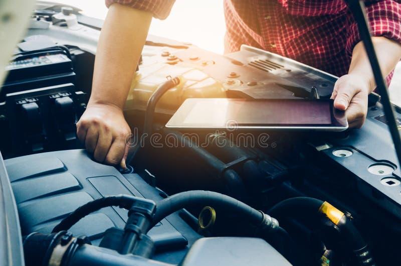 Mens die op een motor van een auto en greeptabletonderzoek controleren naar gegevens stock fotografie