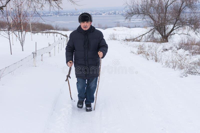 Mens die op een sneeuwweg lopen die houten stok 2 gebruiken stock fotografie
