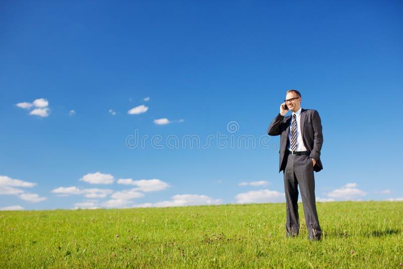 Mens die op een zonnig groen gebied telefoneren stock foto