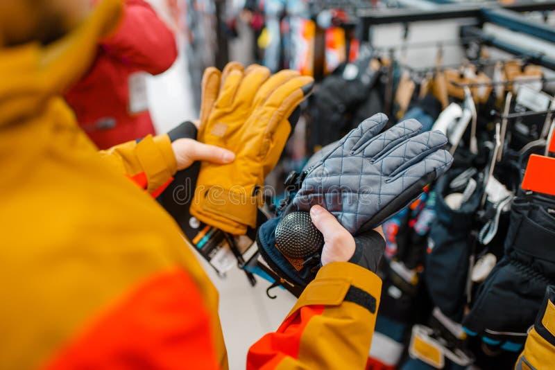 Mens die op handschoenen voor ski of het snowboarding proberen royalty-vrije stock fotografie