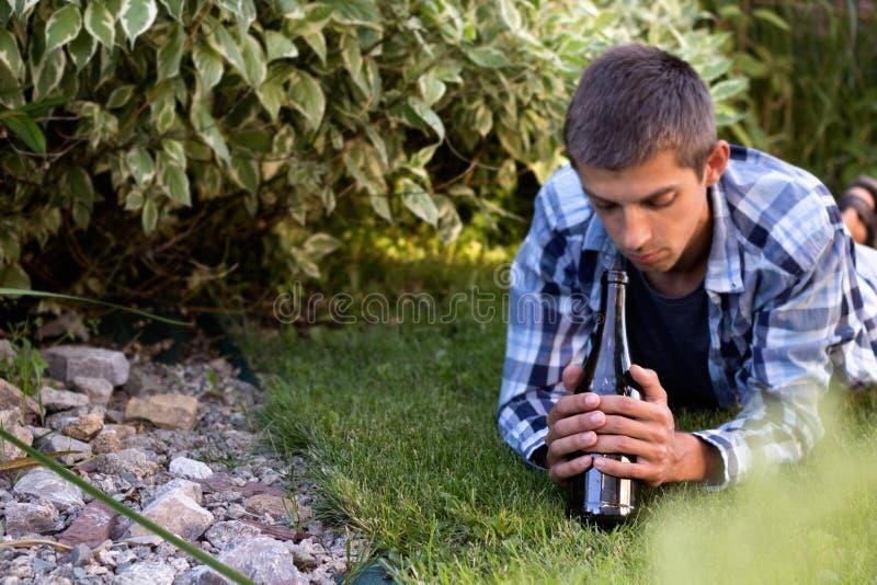 Mens die op het gazon in de het park en het drinken wijn liggen stock afbeeldingen