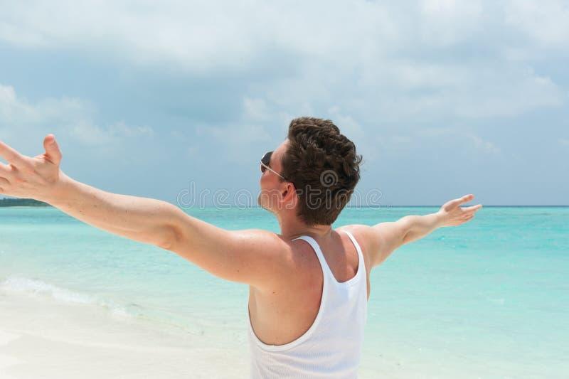 Mens die op het strand met open wapens lopen die van het weer genieten stock fotografie