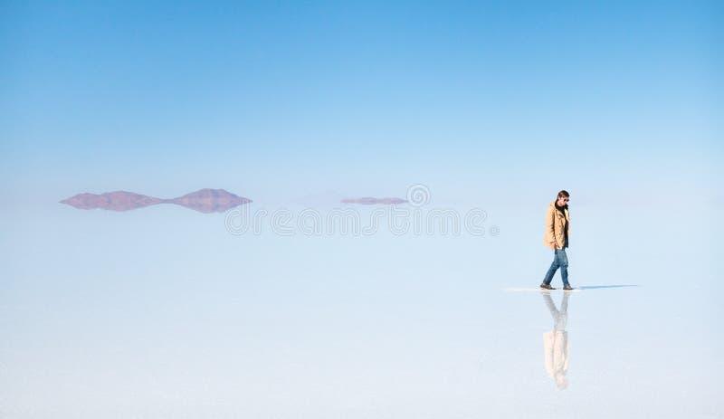 Mens die op het water in Uyuni loopt royalty-vrije stock fotografie