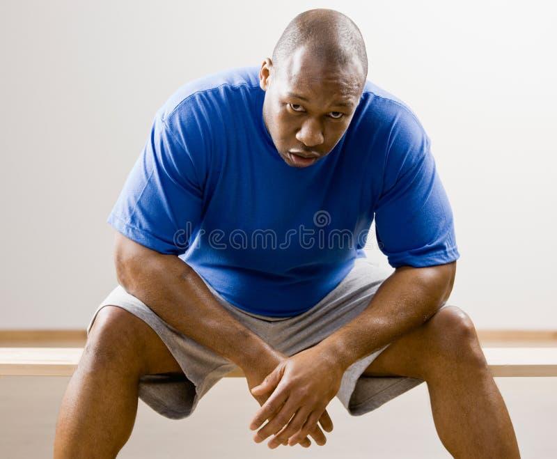 Mens die op knieën in gezondheidsclub leunt stock foto