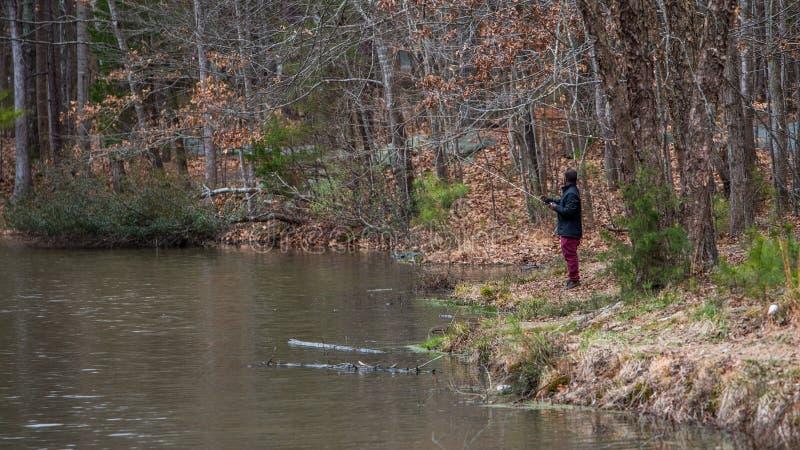 Mens die die op meer vissen door dode bladeren in de winter wordt omringd royalty-vrije stock foto