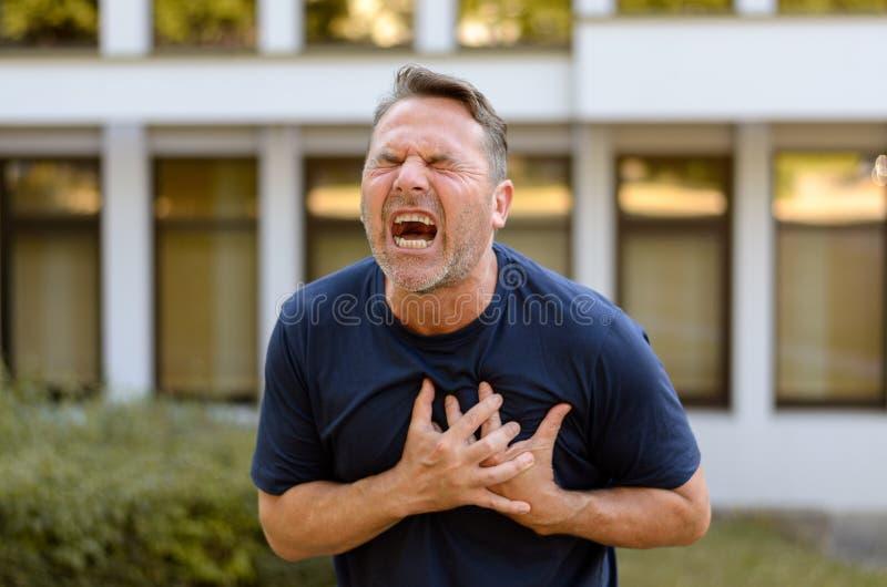 Mens die op middelbare leeftijd aan een hartaanval lijden royalty-vrije stock fotografie