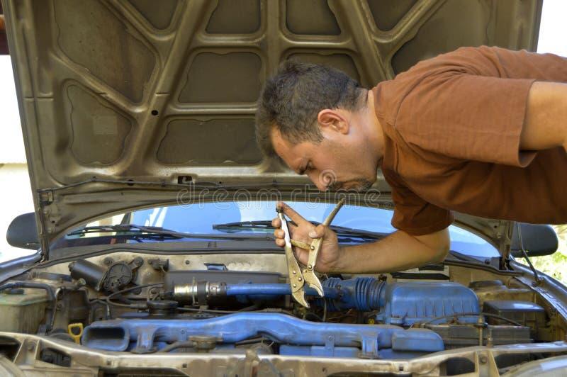 Mens die op middelbare leeftijd hun eigen auto's proberen te herstellen stock fotografie