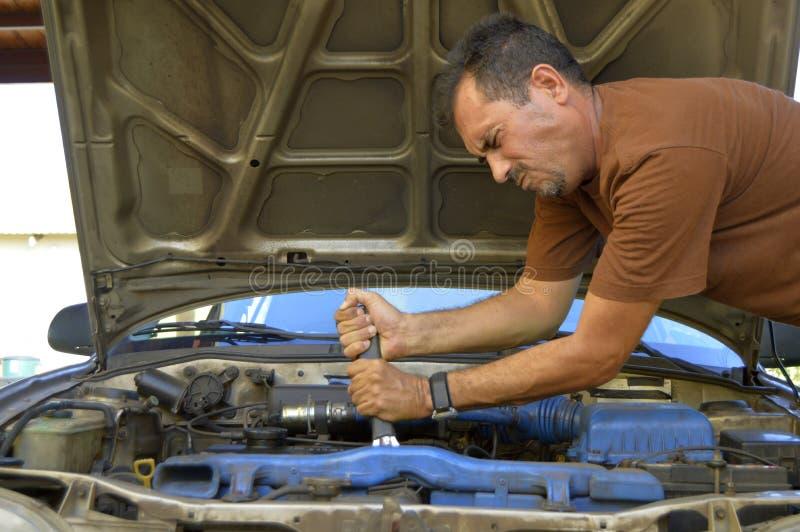 Mens die op middelbare leeftijd hun eigen auto's proberen te herstellen stock foto's