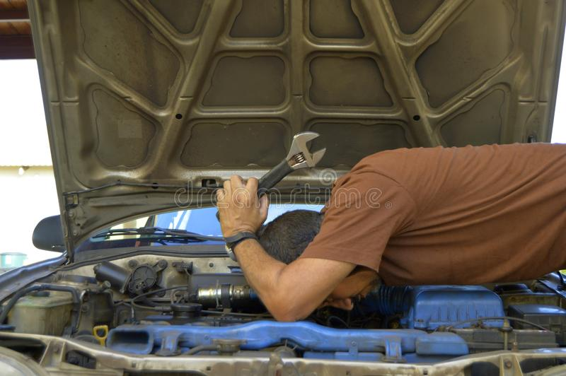 Mens die op middelbare leeftijd hun eigen auto's proberen te herstellen stock foto