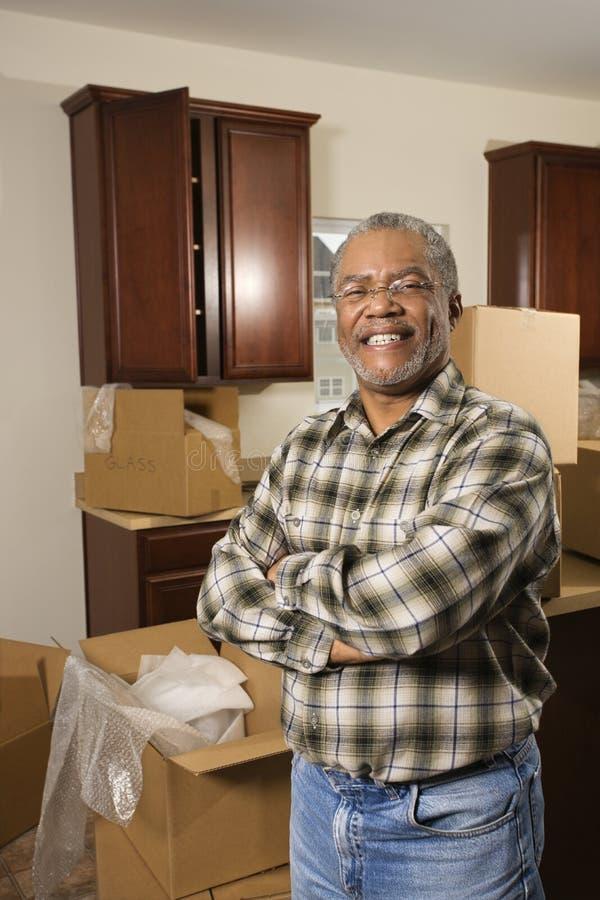 Mens die op middelbare leeftijd zich in keuken met dozen bevindt. stock foto