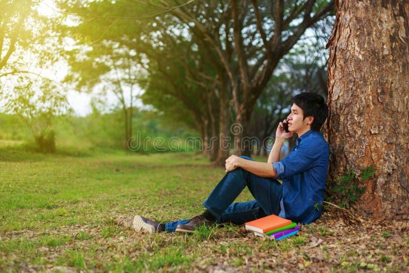 Mens die op mobiele telefoon in park spreken stock afbeelding