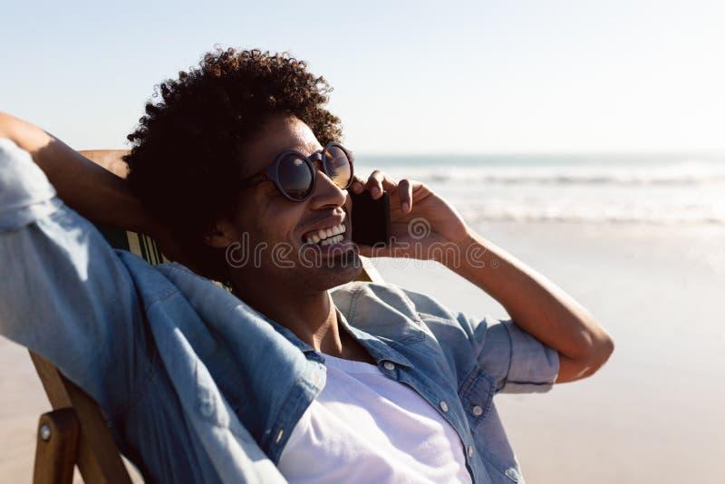 Mens die op mobiele telefoon spreken terwijl het ontspannen in een ligstoel op het strand royalty-vrije stock fotografie