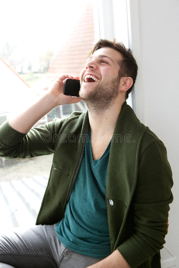 Mens die op mobiele telefoon thuis spreken stock afbeeldingen