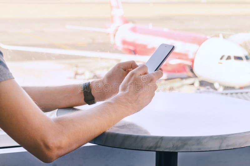 Mens die op mobiele telefoon op zijn vlucht bij luchthaven wachten Mannelijke handen die smartphone, vliegtuig onscherpe achtergr stock foto