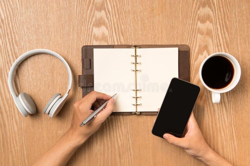 Mens die op notitieboekjezitting die schrijven op lijst, hand slimme pho houden stock fotografie