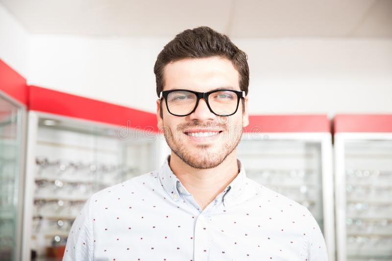 Mens die op oogglazen bij optometristen het glimlachen proberen royalty-vrije stock afbeelding