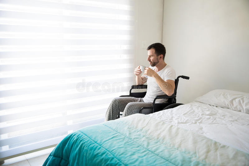 Mens die op rolstoel wat koffie drinken stock afbeelding
