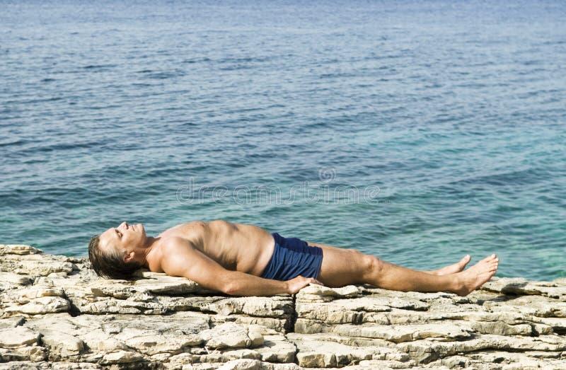 Mens die op rotsen zonnebaadt stock afbeelding