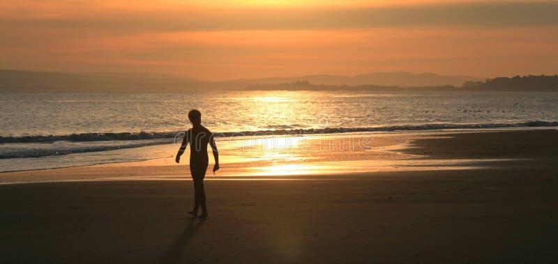 Mens die op strand loopt stock afbeelding