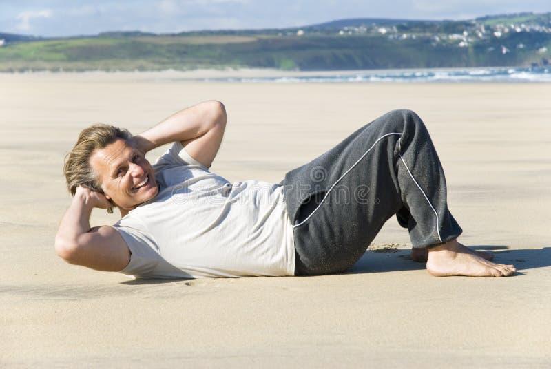 Mens die op strand uitoefent. royalty-vrije stock afbeelding