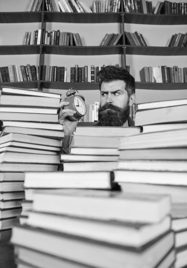 Mens die op strikt gezicht klok, boekenrekken op achtergrond bekijken Uiterste termijnconcept Leraar of student met baard het bes royalty-vrije stock afbeeldingen