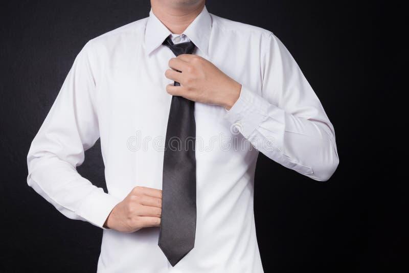 Mens die op stropdas zet stock foto