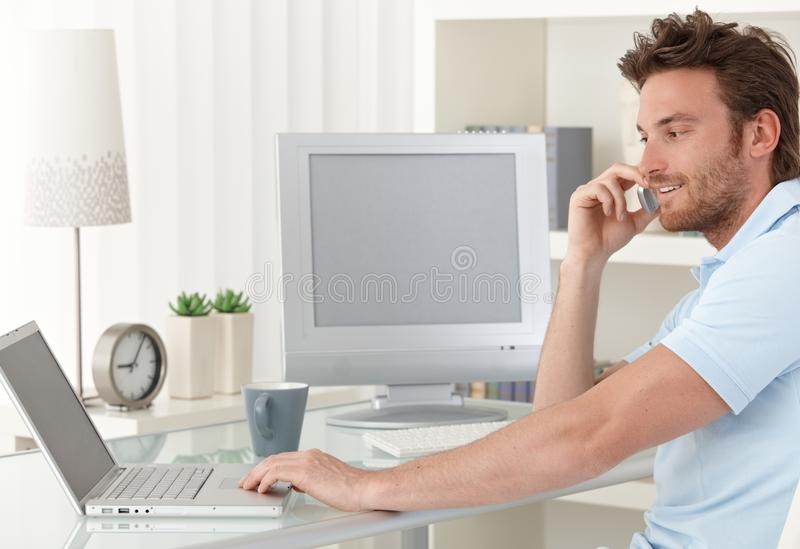 Mens die op telefoon spreekt die computer met behulp van royalty-vrije stock foto's