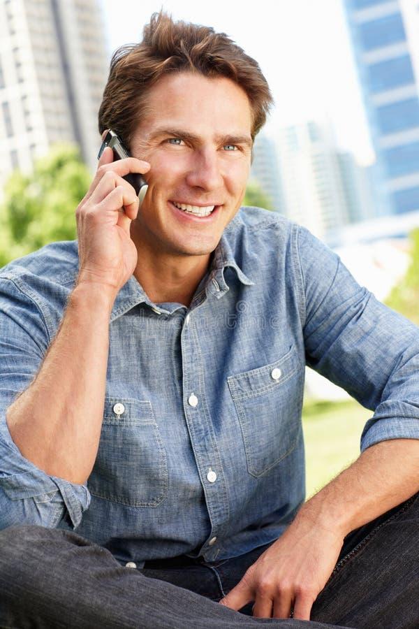 Mens die op telefoon spreekt die in stadspark wordt gezeten stock afbeeldingen