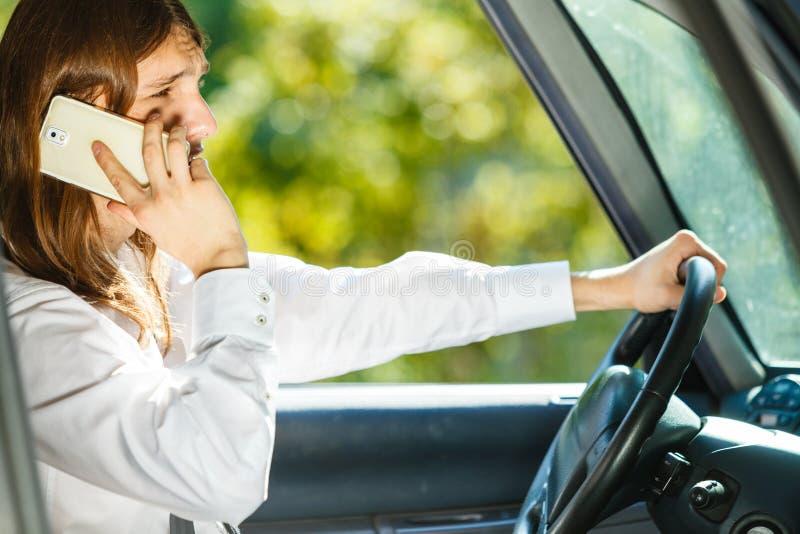Mens die op telefoon spreken terwijl het drijven van auto stock fotografie