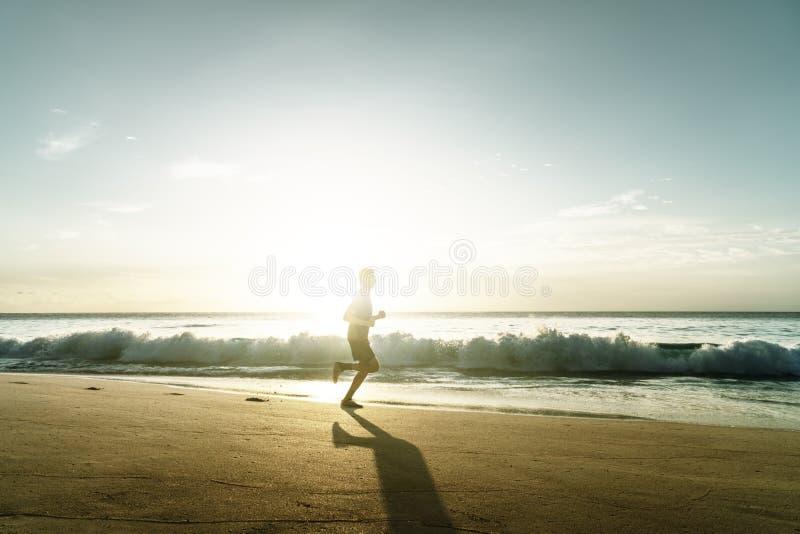 Mens die op tropisch strand bij zonsondergang lopen stock fotografie