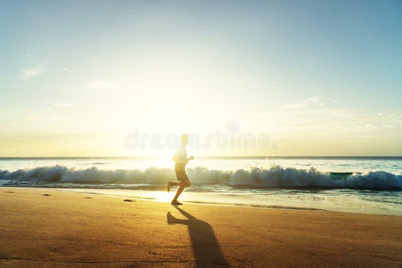 Mens die op tropisch strand bij zonsondergang lopen stock foto
