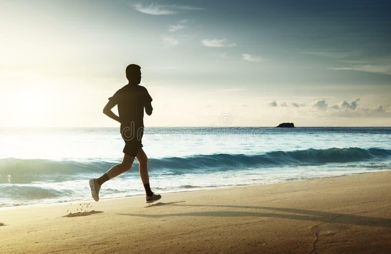 Mens die op tropisch strand bij zonsondergang lopen stock afbeelding