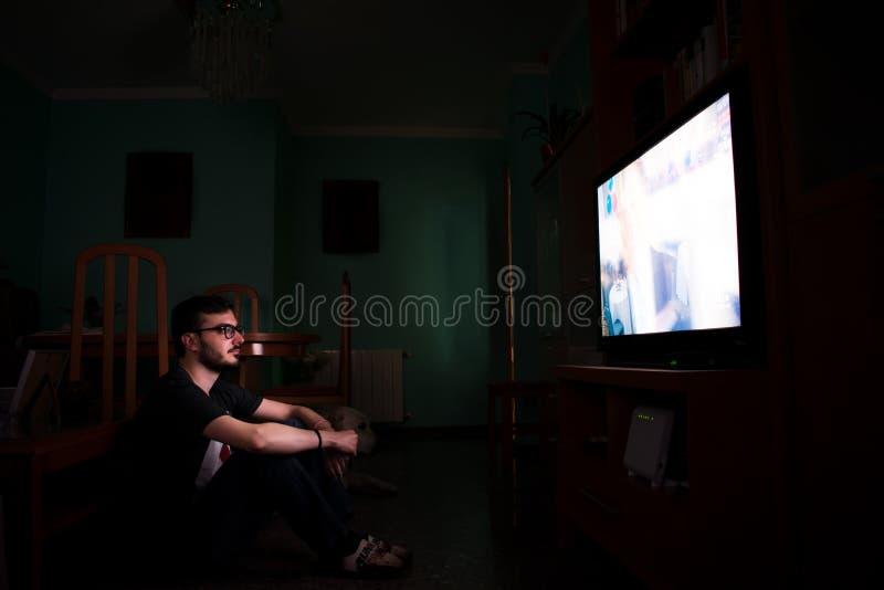 Mens die op TV thuis letten en zitting op de vloer zapping stock fotografie