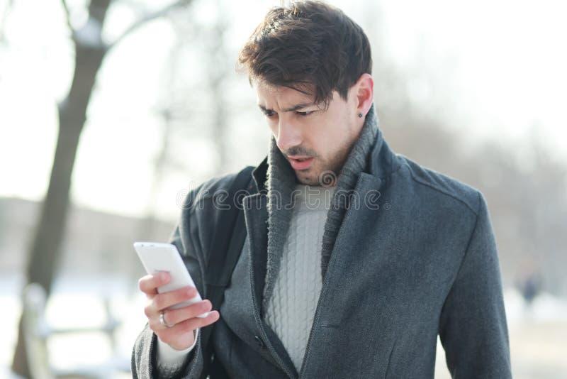 Mens die op zijn smartphone kijken stock foto
