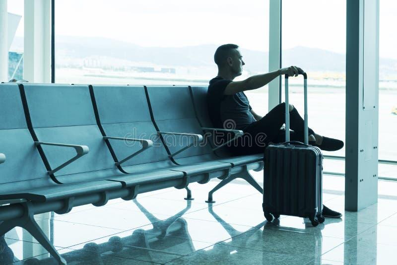 Mens die op zijn vlucht in een luchthaven wachten stock afbeelding