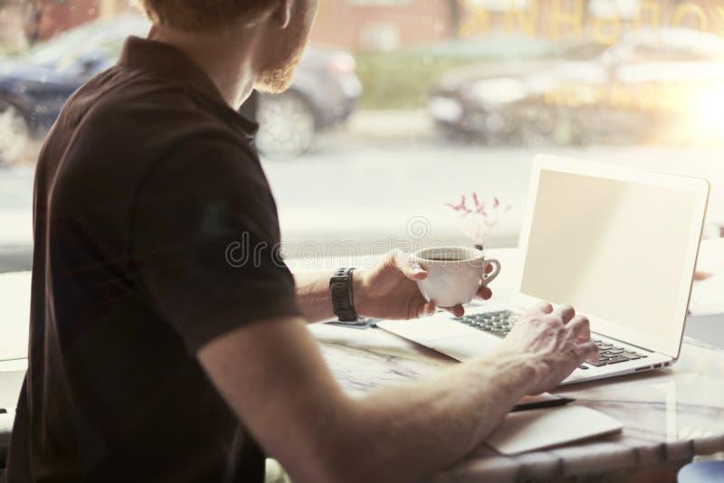 Mens die op zonnig kantoor aan laptop werken terwijl het zitten in koffie die koffie hebben Concept jonge bedrijfsmensen die in o royalty-vrije stock afbeeldingen