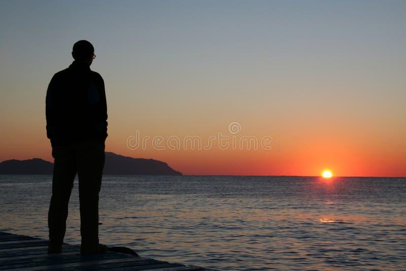 Mens die op zonsondergang kijkt royalty-vrije stock foto's